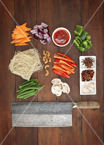 Sliced vegetables, mushrooms, noodles, cashew nuts, spices and a meat cleaver (Asia)