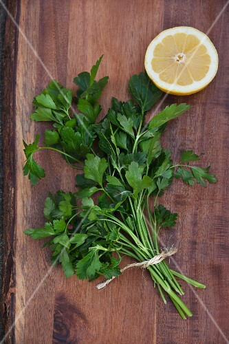 Flat leaf parsley with half a lemon on a wooden board