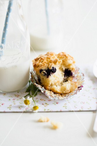 A blueberry and yoghurt muffin with oats next bottle of milk