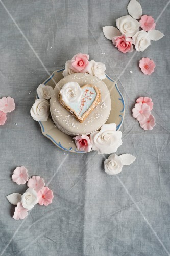 A cake decorated with fondant icing sugar, heart-shaped biscuit and sugar roses