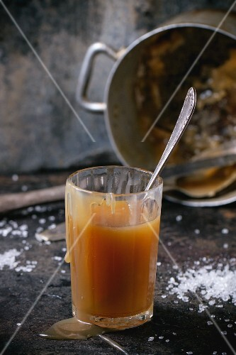 A glass of homemade caramel sauce with an old pot in the background