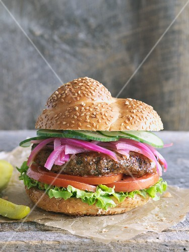 A hamburger with pickled red onions, lettuce and tomatoes