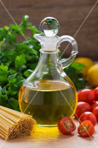 Olive oil, tomatoes, parsley and spaghetti on a wooden table