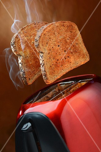 Smoking wholemeal toast jumping out of a red toaster