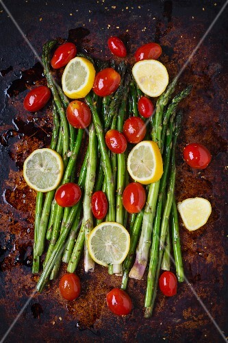 Asparagus, lemon slices and organic grape tomatoes with olive oil and spices on a baking tray