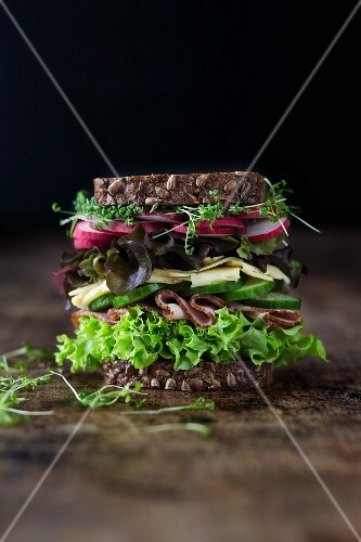A large sandwich with lettuce, ham, cheese, cucumber, radishes and cress on wholemeal bread