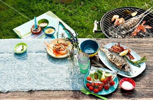 A barbecue in the garden with food on the barbecue and on the table
