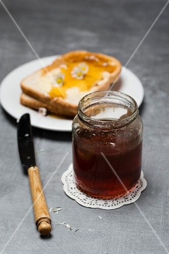 A jar of honey with slices of toast with honey and daisies behind it