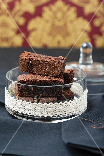 Brownies in a glass bowl decorated with a lace border