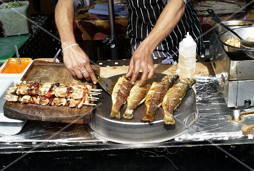 Fried fish and skewers in a street shop at a market (Covent Garden, London)