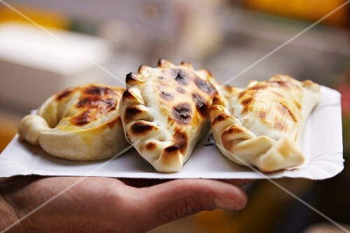 A hand holding a paper plate of empanadas at a market