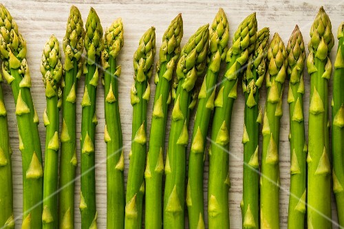 Green asparagus spears on wooden background