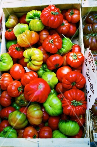 Colourful 'Merinda' tomatoes in a wooden crate at a market in France