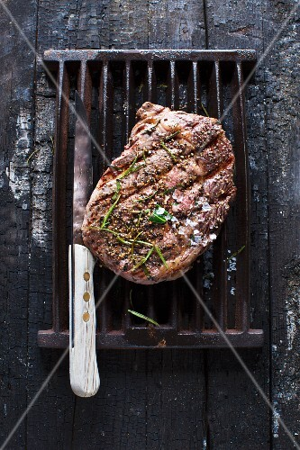 Grilled peppered steak on a grill rack with a knife