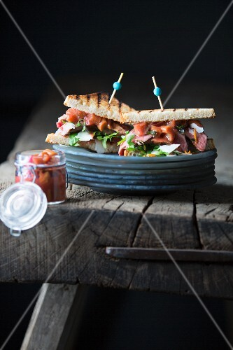 A toasted sandwich with grilled steak and rhubarb chutney on a wooden table