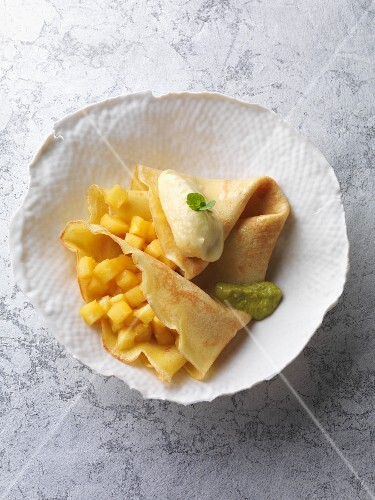 Crepes with a pineapple ragout, passion fruit and coconut ice cream and pistachio sauce