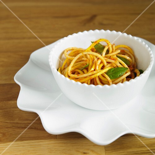Yellow courgette spaghetti with tomato sauce and basil in a white bowl