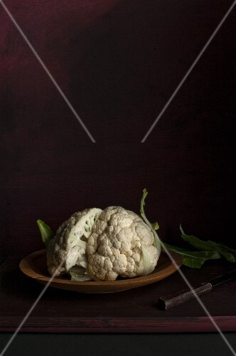 A halved cauliflower in a wooden bowl on a dark surface
