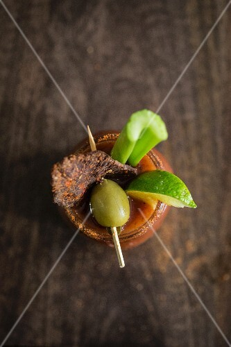 A Bloody Mary with beef jerky, an olive, lime and a stick of celery