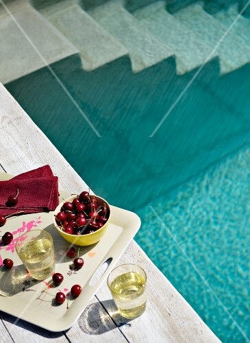 View from above of cherries and drinks on tray on edge of swimming pool