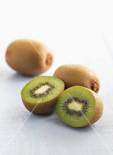 Kiwi fruits, whole and halved