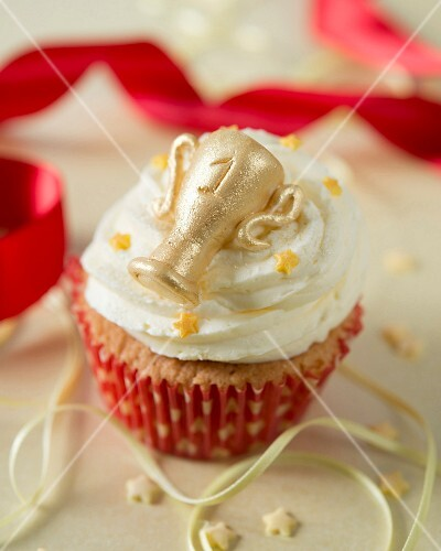 A cupcake decorated with vanilla butter cream and a golden trophy