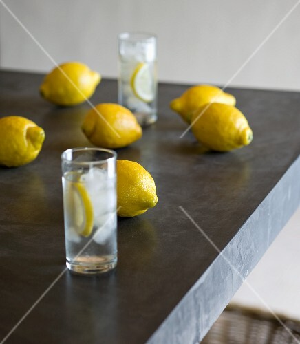 Lemons and glasses of ice water on grey table