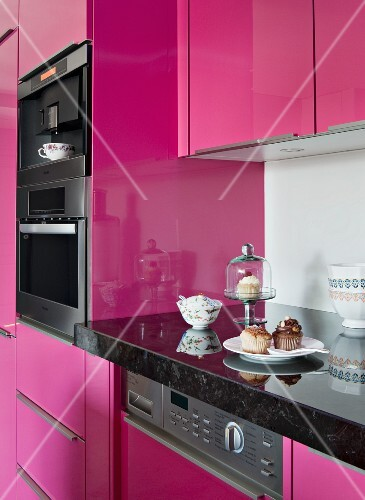 Fitted kitchen with glossy hot pink fronts