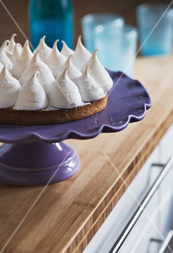 Meringue cake on a cake stand in a kitchen