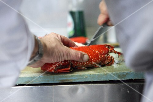 A chef cutting a cooked lobster in half