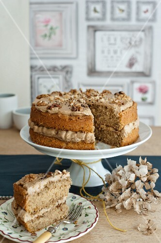 Coffee and walnut cake on a cake stand; sliced