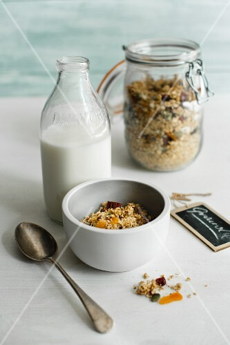 A bowl of muesli with a bottle of milk and a jar of muesli in the background