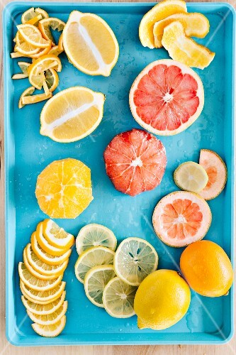 An arrangement of freshly cut lemons, Meyer lemons and grapefruits on a turquoise tray