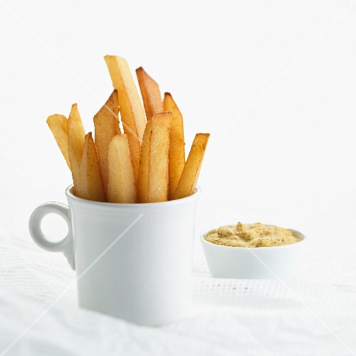 A mug of chips and spicy mustard