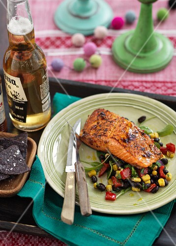 Grilled salmon on a bean salad with black tortilla chips and beer