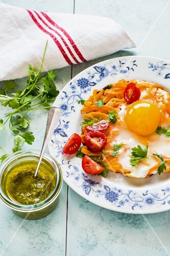 Fried egg and sweet potato fritter with tomatoes