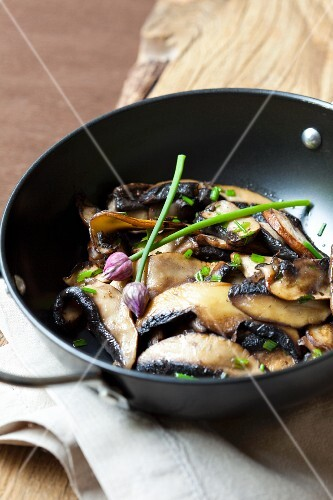 Fried mushrooms with chives in a pan