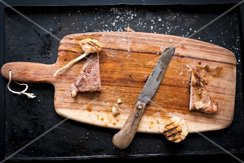 The remains of grilled Iberian pork secreto (fillet steak) with garlic