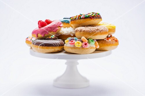 Various colourful doughnuts on a cake stand