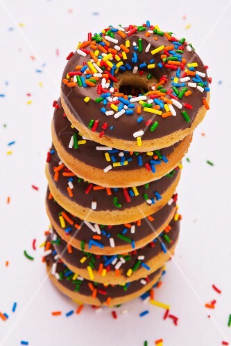 A stack of chocolate-glazed doughnuts with colourful sugar sprinkles