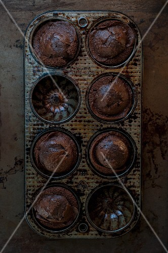 Mini chocolate Bundt cakes in a baking tin (seen from above)