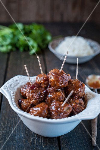 Spicy meatballs on sticks with a side of rice