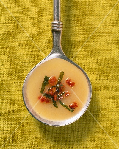 Potato soup with sage and bacon in a ladle