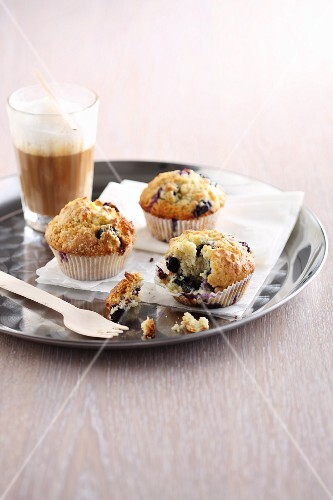 Blueberry muffins with latte macchiato on a tray