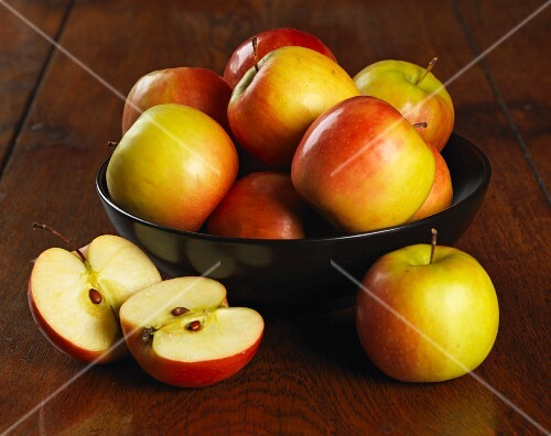 A bowl of fresh apples with one in front cut in half