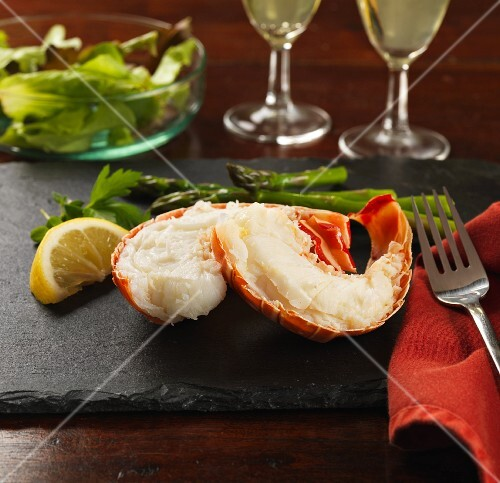 Lobster tails with lemon, asparagus and salad