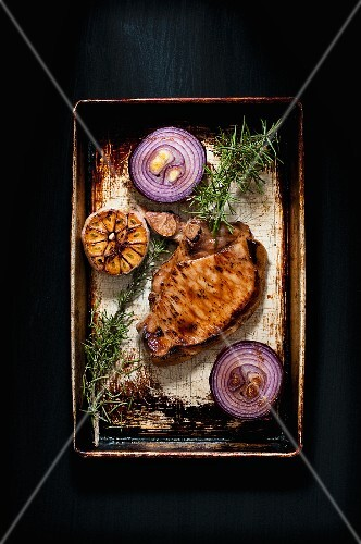 Roasted pork chop with red onions, garlic and rosemary