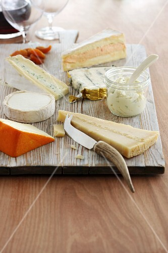 Various types of cheese on a wooden board with a cheese knife