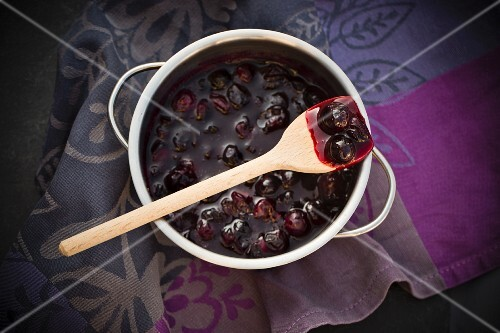 A spoonful of blueberry jam in a pot