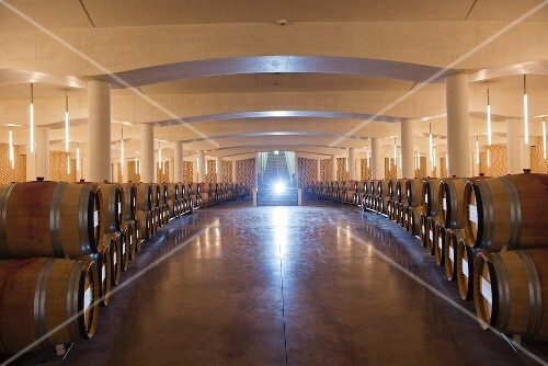 Wine barrels in a cellar at Chateau Cheval Blanc (St-Emilion, Bordeaux, France)
